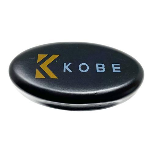 The dark wood handle of Kobe Cagney Beard Brush